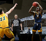 SIOUX FALLS, SD - MARCH 7: Franck Kamgain #11 of the UMKC Kangaroos shoots a jumper over Jarius Cook #11 of the North Dakota State Bison during the Summit League Basketball Tournament at the Sanford Pentagon in Sioux Falls, SD. (Photo by Dave Eggen/Inertia)