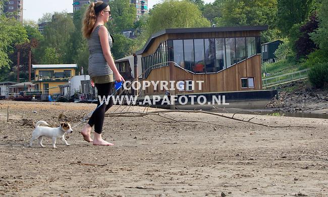 Nijmegen 260411 Droogte en lage stand van de Waal.<br /> Woonbootbewoner Sharon laat haar hondje Chucky uit rondom haar woonboot die grotendeels op het droge staat.<br /> Foto frans Ypma APA-foto