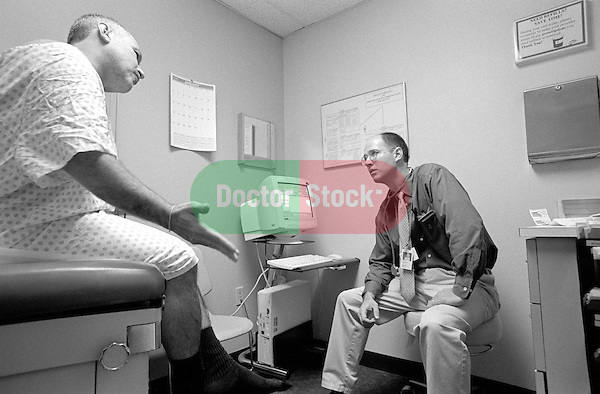 Middle age male patient seated on examination table speaking with and gesturing to young male doctor in examination room