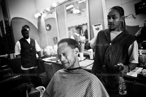 Chicago Illinois <br /> USA<br /> June 2008 <br /> <br /> Barber Michael Matthews cuts Reginald Robinson hair at Bulls Eye Barber Shop on 79th Street. Chicago is the largest city by population in the state of Illinois and the American Midwest, United States. It is a dominant center of finance, industry and culture in the region. It is currently ranked as the third-most populous city in the United States after New York and Los Angeles, with a population of nearly 3 million people.