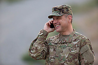 Man in US military uniform, happy talking on a mobile phone. DoD compliant for advertising, model released.