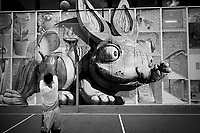 Switzerland. Canton Ticino. Lugano. A young black teenage boy is practicing basketball. On the wall, a mural painting of a giant rabbit, two small teddybears, two guitars and Sam's face.12.05.2020 © 2020 Didier Ruef