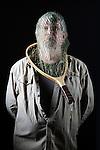 Selfie, self portrait by Douglas Orton on dark background in harsh light.  Antique fishing net on head.