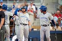 Dunedin Blue Jays catcher Riley Adams (23) high fives Bradley Jones (center) after hitting a grand slam home run in the top of the fourth inning during a game against the Charlotte Stone Crabs on June 5, 2018 at Charlotte Sports Park in Port Charlotte, Florida.  Also shown is Nash Knight (background) and Ivan Castillo (right).  Dunedin defeated Charlotte 9-5.  (Mike Janes/Four Seam Images)