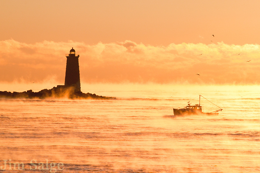 A lone lobster boat is out in Portsmouth Harbor on a day that began below zero.  Sea smoke surrounds them as they check their pots.