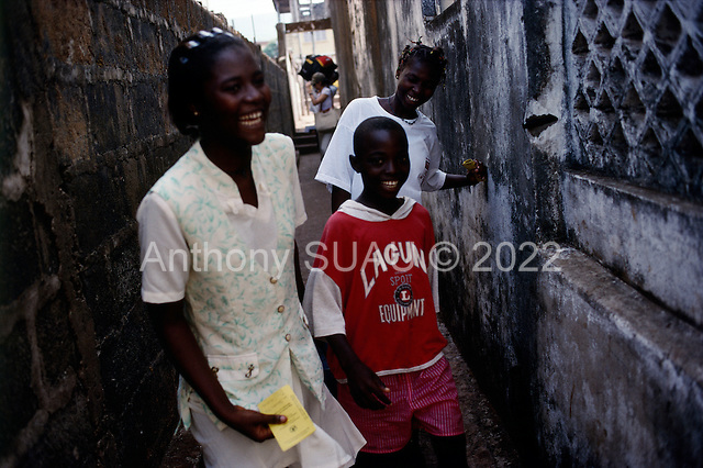 Freetown, Sierra Leone<br /> April 2001<br /> <br /> Jalikaou Tity Turay, 18  and her sister N'yillah Turay, 16 are reunited with their mother Yeabu Turay in Freetown, Sierra Leone after 3 years in Guinea as war refugees. The two girls enter their old home as Jalikaou Tity Turay, 18  enters the house with her brother.