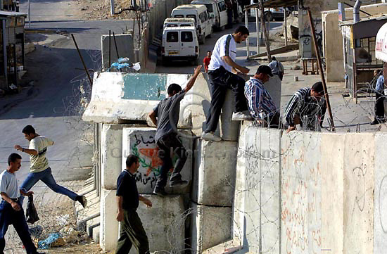 Palestinians cross the wall built to separate the Palestinian territories from Israel, June 1,2003, in the West Bank neighbourhood of Abu Dis, next to Jerusalem, as they return from illegal work in Israel. Photo by Quique Kierszenbaum