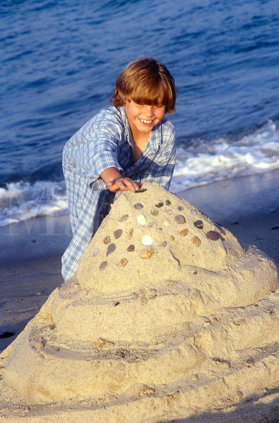Boy building a sand castle at the beach.