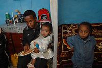 etiopia, addis abeba, ragazzo con le sorelle nella sua casa.Boy and his sistes in their home