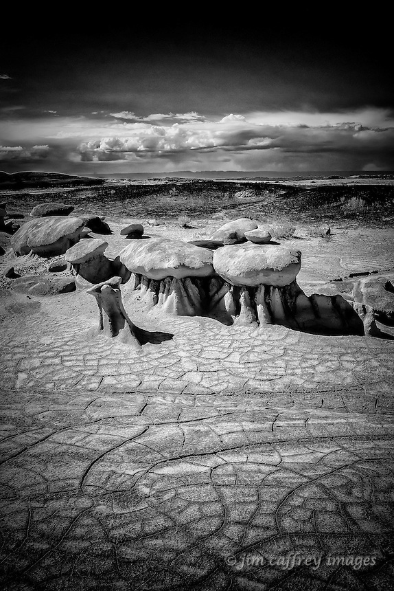A black and white image of small hoodoos in Alamo Wash with cracked earth in the foreground and building storm clouds in the distance.