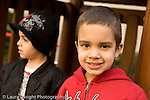 Preschool backyard playground children playing in early spring ages 3-5 New York City portrait of boy looking at camera with friend in background horizontal