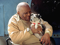 Elderly African-American man smiling and holding a pet therapy dog.