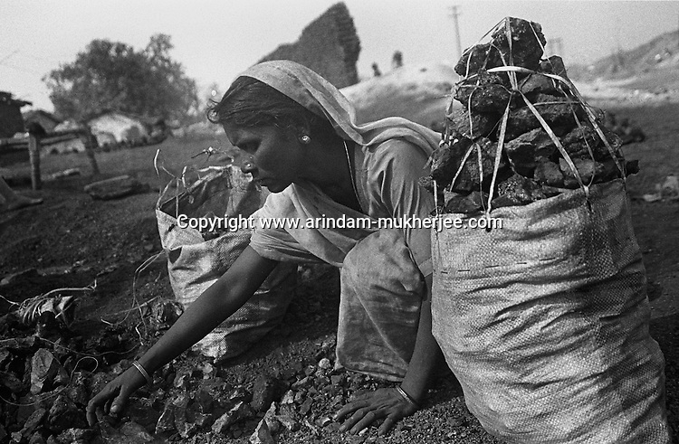 A woman gathering coal, which are to be carried to be sold in the nearby illegal coal market. Bhagatdih Colliery area, Jharia, Jharkhand, India. Arindam Mukherjee