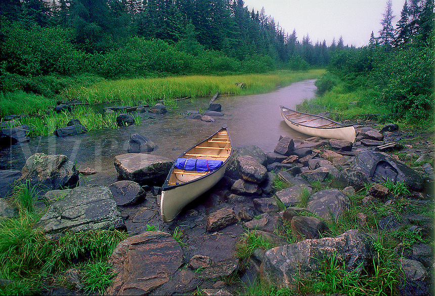 Canoes in rocky stream.