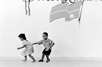Republic of Nauru. Central Pacific. Nauru is a tiny island (21 square-km). A boy and a girl play near a wall where a painting represents Nauru's flag. The indigenous people of Nauru customarily comprise twelve tribes symbolised by the twelve-pointed star on the national flag. © 1999 Didier Ruef