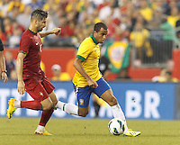 Brazil substitute midfielder Lucas Moura (7) dribbles as Portugal midfielder Miguel Veloso (4) defends. In an international friendly, Brazil (yellow/blue) defeated Portugal (red), 3-1, at Gillette Stadium on September 10, 2013.