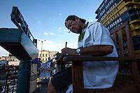 Balanceiro da feira do ver-o-peso, conferindo suas anotações no final do expediente. Local: Belém-PA, Data: 03/11/2012, Foto: Ana Mokarzel
