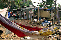 A discarded Philippine flag that found a new life as a hammock lies amid the ruins of a squatter area fronting the main gate of the House of Representatives in Batasan Hills, Quezon City. The squatters forcibly removed from the area days before the visit of US President George W. Bush are returning and rebuilding, as evidenced by a woman planting a post for her shack in the background. 21 October 2003