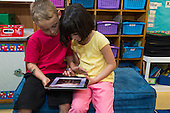 MR / Schenectady, NY. Zoller Elementary School (urban public school). Kindergarten inclusion classroom. Students read an eBook / app on an iPad. Left: boy, 5; Right: girl, 5. MR: Bur12, Coh2. ID: AM-gKw. © Ellen B. Senisi.