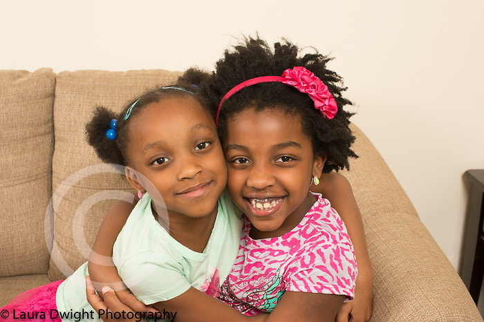 Portrait of two sisters, ages 6 and 7, hugging