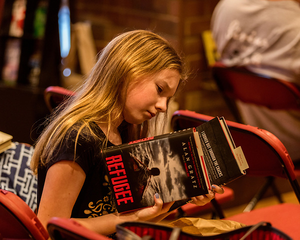 """July 26, 2017. Raleigh, North Carolina.<br /> <br /> Allí Lambert, age 12, checks out copies of two of Alan Gratz's books.<br /> <br /> Author Alan Gratz spoke about and signed his new book """"Refugee"""" at Quail Ridge Books. The young adult fiction novel contrasts the stories of three refugees from different time periods, a Jewish boy in 1930's Germany , a Cuban girl in 1994 and a Syrian boy in 2015."""