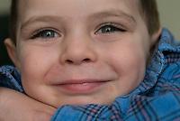 boy in blue flannel shirt smiles