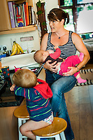 A mother breastfeeds her baby while standing up chatting in her kitchen.<br /> <br /> 30 August 2012<br /> Hampshire, England, UK