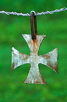 A metal Iron Cross hangs from the fence in the cemetery at St. Josephs Church in Somerset, Ohio. The church is the oldest Catholic church in Ohio...<br />