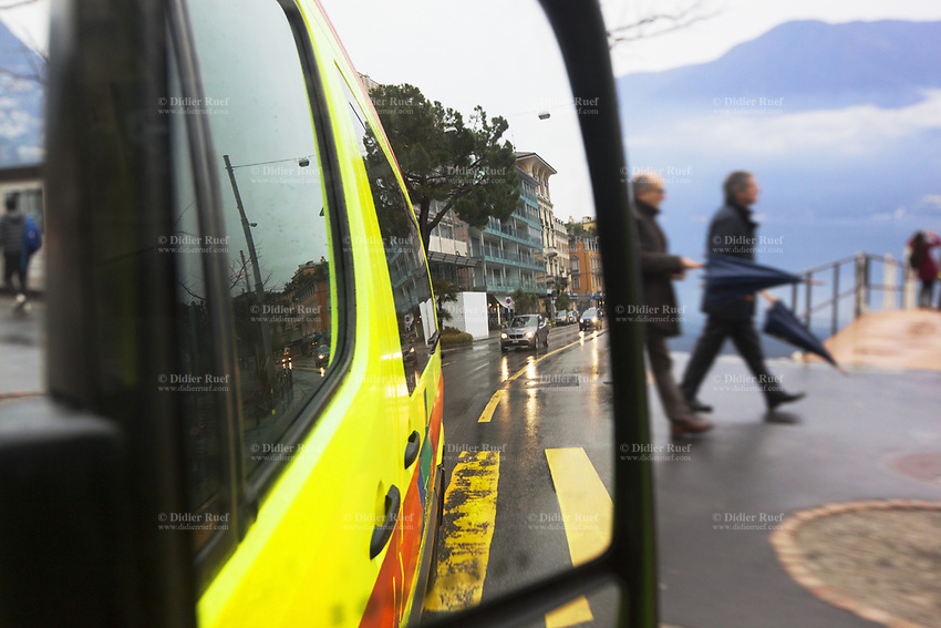 Switzerland. Canton Ticino. Lugano. View through a side mirror on an ambulance ride during a medical emergency intervention. The ambulance belongs to the Croce Verde Lugano. Mirror reflection. Tourists walk on the sidewalk near the lake. TheCroce Verde Lugano is a private organization which ensure health safety by addressing different emergencies services and rescue services. Lake Lugano (or Lake Ceresio ) is a glacial lake. 27.01.2018 © 2018 Didier Ruef