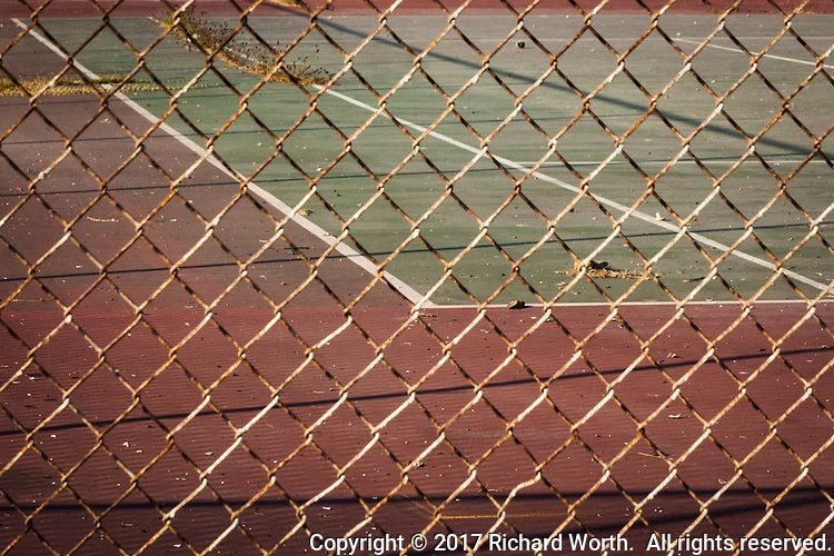 Behind a rusting chain link fence lies an abandoned tennis court with scattered debris and weeds and its distinctive lines: service line, singles line, doubles.