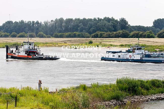 WESTERVOORT 030712 De tanker dat op de kop van de rivier de IJssel tussen Huissen en Westervoort vast lag, wordt losgetrokken door een sleepboot.<br /> Foto Jorrit Knuvelder - APA Foto