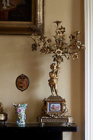 A rococo candelabra formed of a gilt boquet of flowers on the morning room mantelpiece