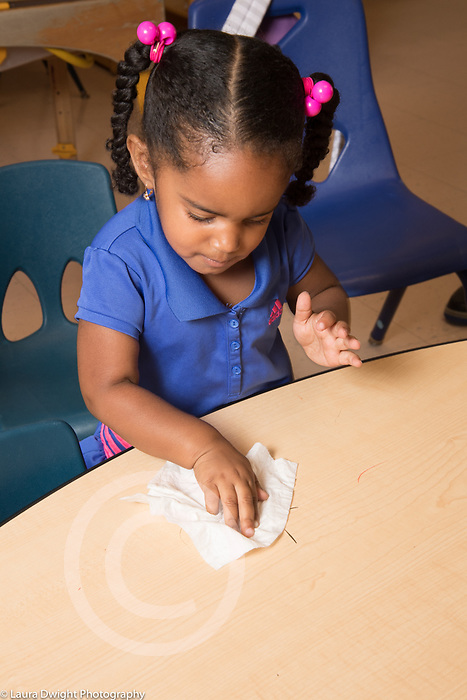 Education Preschool 3 year olds boy cleaning table surface
