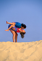 Mother and daughter having fun on a sand dune by the beach.