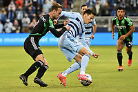KANSAS CITY, KS - MAY 9: Daniel Salloi #20 Sporting KC with the ball watched by Tomas Pochettino #7 Austin FC during a game between Austin FC and Sporting Kansas City at Children's Mercy Park on May 9, 2021 in Kansas City, Kansas.