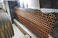 A big stack of bottles stored laying down stacked piled high in terracotta earthenware tube containers. Vita@I Vitaai Vitai Gangas Winery, Citluk, near Mostar. Federation Bosne i Hercegovine. Bosnia Herzegovina, Europe.