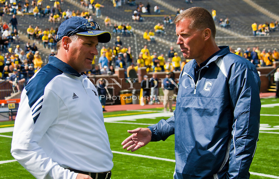 Michigan head coach Rich Rodriguez, left, speaks with Connecticut head coach Randy Edsall, before their NCAA college football game, Saturday, Sept. 4, 2010, in Ann Arbor, Mich. (AP Photo/Tony Ding)