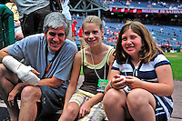 24 May 2009: Washington Nationals' Team Photographer Mitchell Layton (left) sits on the steps of the dugout with his daughter (right) and her friend (center) prior to a game against the Baltimore Orioles at Nationals Park in Washington, DC. Layton, coming off hand surgery, is wearing a cast due to a foul ball injury suffered earlier in the week. The Nationals rallied to defeat the Orioles 8-5 and salvage one win of their interleague series. Mandatory Credit: Ed Wolfstein Photo