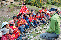 A Backroads Active Travel guide, Paulo, jokes around with a group of boys from the high Andes weaving village of Huilloc in Peru.