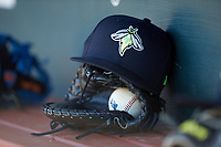 A Columbia Fireflies cap sits on top of a glove in the home dugout during the South Atlantic League game against the Rome Braves at Segra Park on May 13, 2019 in Columbia, South Carolina. The Fireflies walked-off the Braves 2-1 in game one of a doubleheader. (Brian Westerholt/Four Seam Images)
