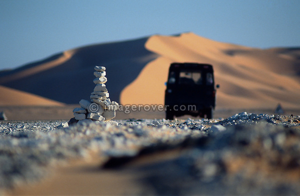 Africa, Algeria, Sahara Desert. Series Land Rover passing a traditional stone roadsign on a typical rough dirt road contrasting against the beautiful setting of the pituresque Sahara sand dunes. --- No releases available, but release may not be required. Automotive trademarks are the property of the trademark holder, authorization may be needed for some uses.