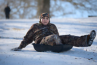David Newton, 10, of Prairie Grove reaches to steer himself Friday, Feb. 19, 2021, as he slides downhill in an animal feed trough while sledding with his family at Battlefield State Park in Prairie Grove. The Newtons were taking a break from virtual instruction to take advantage of the good sledding conditions before warm temperatures melted the snow from the hillside. Visit nwaonline.com/210220Daily/ for today's photo gallery. <br /> (NWA Democrat-Gazette/Andy Shupe)