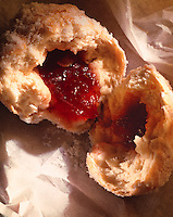 upright close up of a jam donut broken in half with fruit jam pouring out