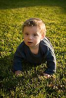 Baby boy crawling across grass towards camera