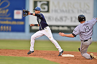 Asheville Tourists shortstop Emerson Jimenez #14 receives the throw and attempts to apply the tag as Carl Thomore #13 slides in safely during a game against the Kannapolis Intimidators at McCormick Field on June 5, 2014 in Asheville, North Carolina. The Intimidators defeated the Tourists 5-3. (Tony Farlow/Four Seam Images)