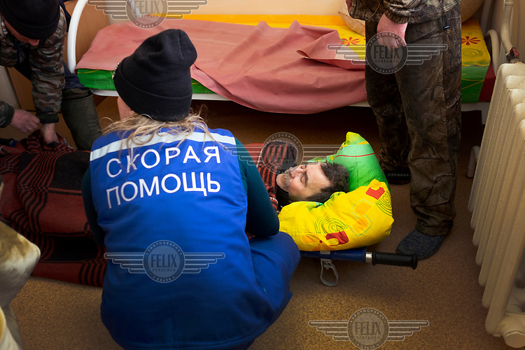 Paramedic Lyuba covers a patient with blanket before the two hour helicopter flight to Turukhansk hospital.