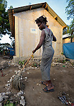 A survivor of Haiti's devastating earthquake, Olginne Pierre sweeps in front of a new house in Leogane, south of the Haitian capital of Port-au-Prince. The houses here were built with assistance from the Christian Reformed World Relief Committee, a member of the ACT Alliance. CRWRC is planning more than 1700 houses in the community, and had about half that number completed by the first anniversary of the January 21, 2010 quake. The houses are built on the foundations of the residents' former homes, and are transitional--designed to be improved by residents as they are able. The houses have yet to receive their first coat of paint. CRWRC has also worked with community members on water and sanitation issues in response to the cholera outbreak, and is providing psycho-social support for residents as they rebuild their lives.