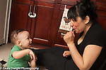 10 month old baby boy sitting with mother on kitchen floor singing song with hand gestures
