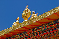 Wheel of Law with two deer represent the Buddha's first teaching of the Middle Way in Deer Park, India, on the roof of Takten Migyu Potrang, or New Summer Palace of the 14th Dalai Lama, at Norbulingka, founded by the 7th Dalai Lama in 1755, Lhasa, Tibet, China.