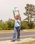 May 5, 2018. Fayetteville, North Carolina.<br /> <br /> Katie Gallagher, of Hampstead, NC, holds a sign about the GenX pollution of the Cape Fear River on Hwy. 87 just outside the Chemours plant which has been dumping GenX unregulated into the river for years. <br /> <br /> The Chemours Company, a spin off from DuPont, manufactures many chemicals at its plant in Fayetteville, NC. One of these, commonly referred to as GenX, is part of the process of teflon manufacturing. Chemours has been accused of dumping large quantities of GenX into the Cape Fear River and polluting the water supply of city's down river and allowing GenX to leak into local aquifers.